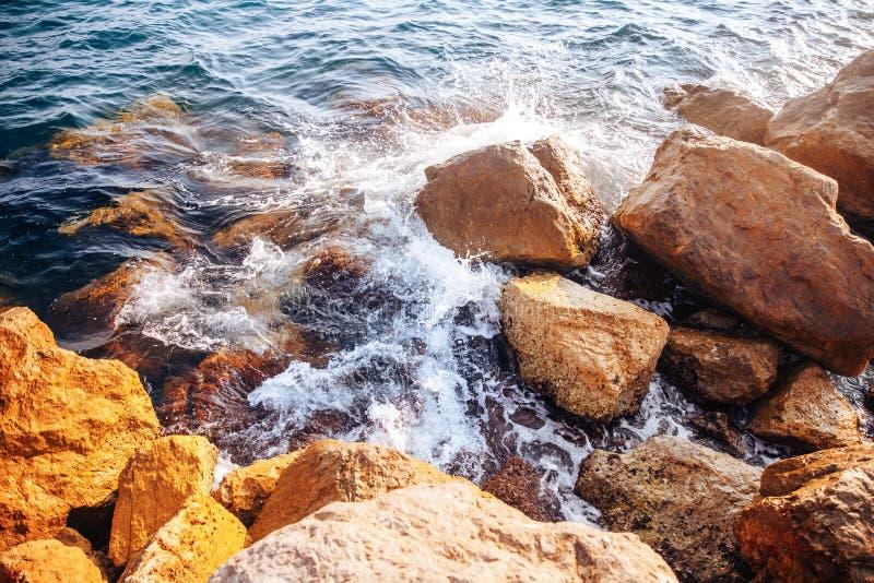 Бурное море с волнами и брызгает перерывы на острых камнях, теплый день, свет солнца стоковое изображение rf