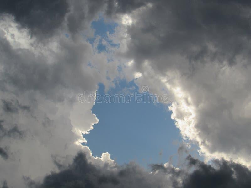 Бурное небо с турбулентными серыми облаками и отверстием голубого неба стоковое изображение rf