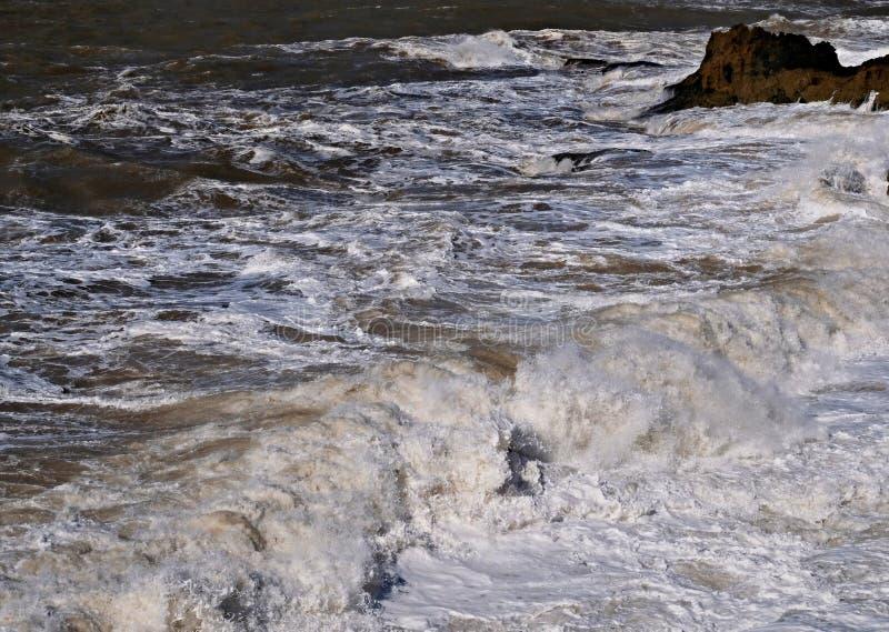 Бурные волны с брызгают и пена на поверхности океана во время шторма стоковое фото rf