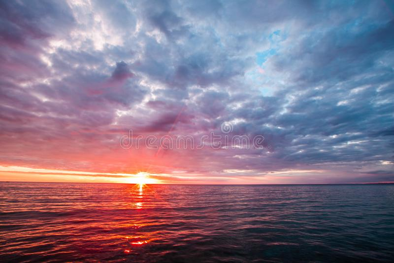 Бурные облака над спокойными водами при солнце касаясь горизонту Минималистский Seascape стоковое фото rf
