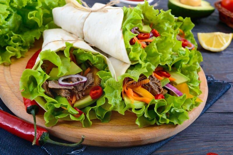 Буррито с прерванным мясом, авокадоом, овощами, горячим перцем на разделочной доске на темной деревянной предпосылке стоковые изображения rf