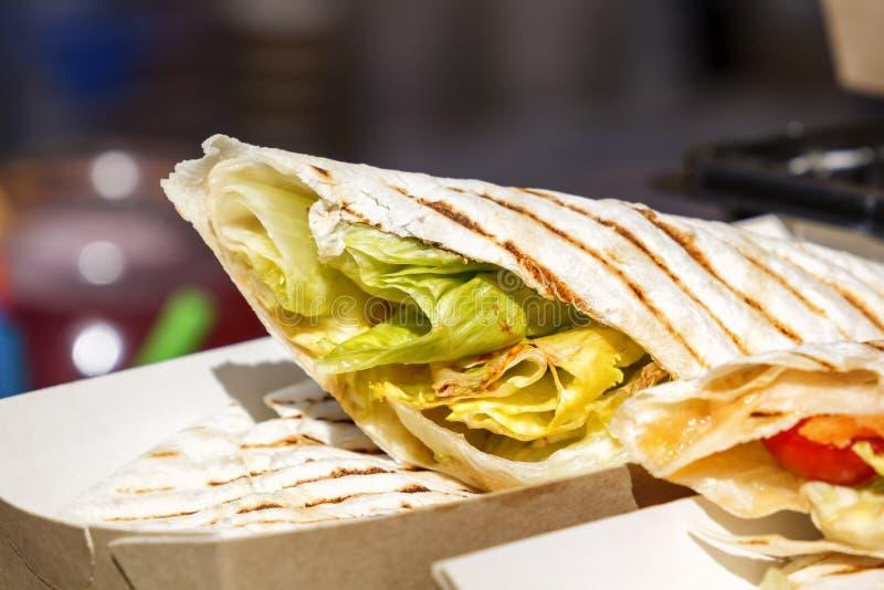 Буррито фаст-фуда улицы с большими листьями и овощами салата на счетчике кафа стоковые фото