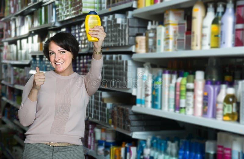 Бутылка брюнет женская выбирая шампуня в супермаркете стоковые фото