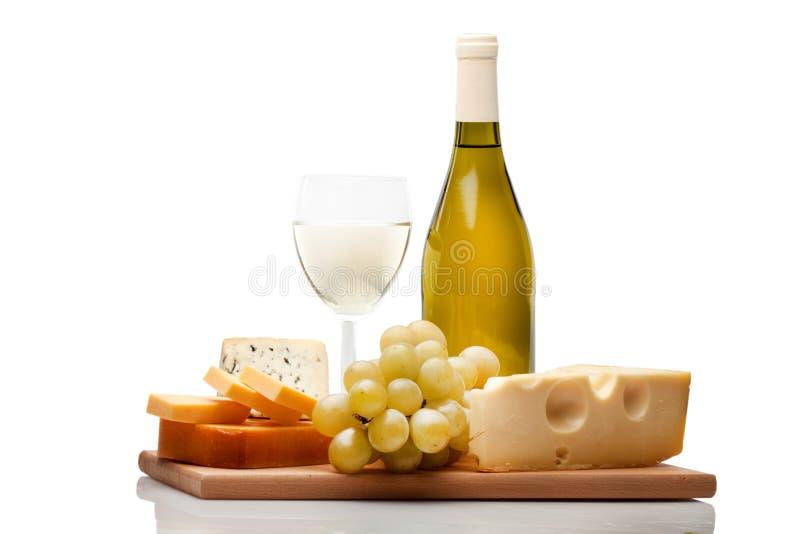 Бутылка вина, бокал, сыр и виноградина на стоковые фотографии rf