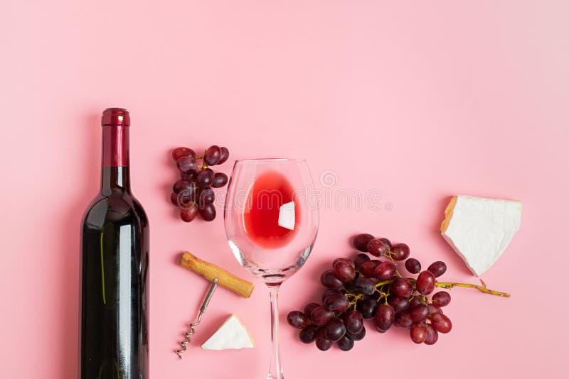 Бутылка вина пустое стекло связка винограда куски сыра на нежной розовой предпосылке minimalism r стоковые фото