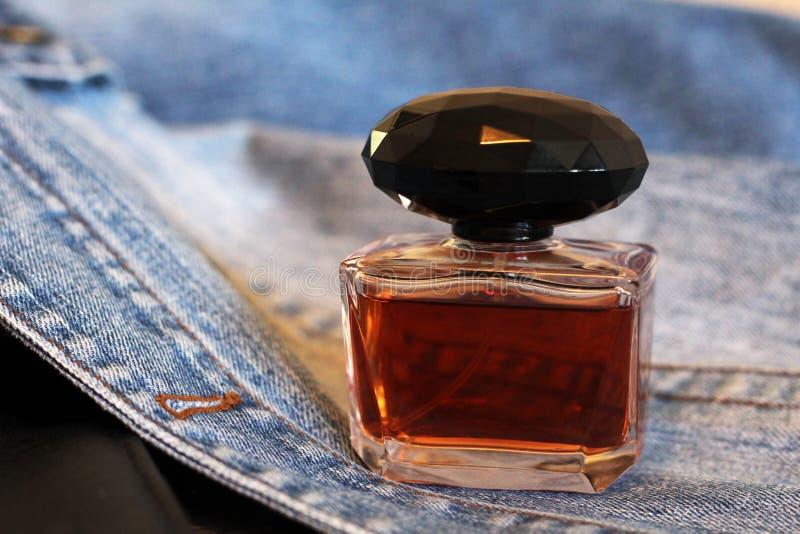 Бутылка духов на джинсах, коричневого цвета стоковые изображения rf