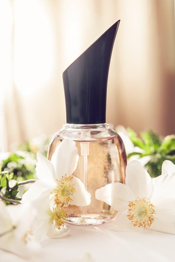 Бутылка дух с белыми цветками Флористическое благоухание Естественная концепция косметик стоковое изображение rf