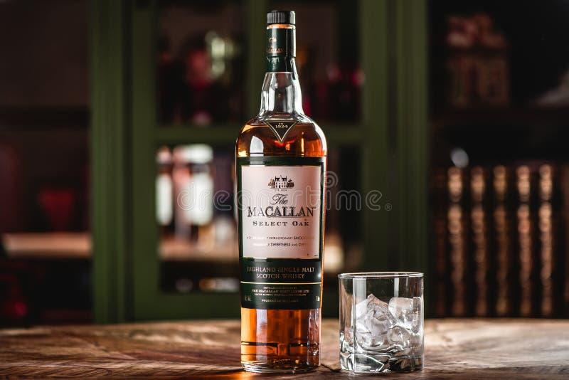 Бутылка и стекло вискиа Macallan с кубами льда на деревянном t стоковые фотографии rf