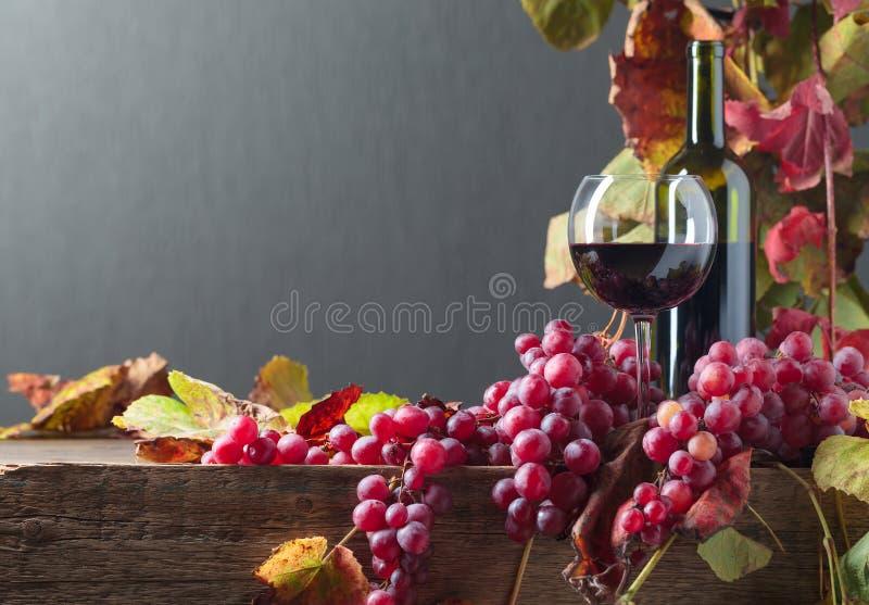 Бутылка и стекло красного вина и виноградин с листьями лозы на старом деревянном столе стоковые изображения