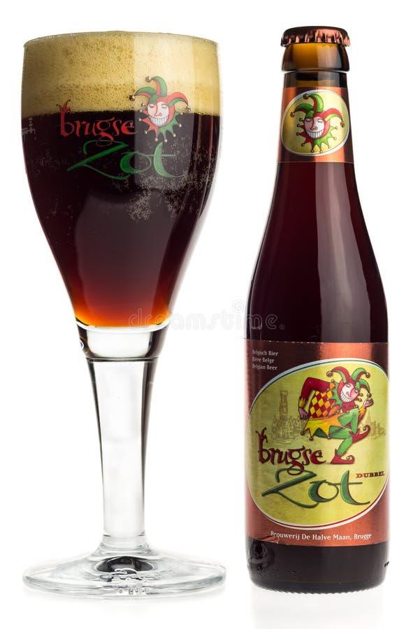Бутылка и стекло пива Brugse Zot Dubbel изолированного на белизне стоковое фото