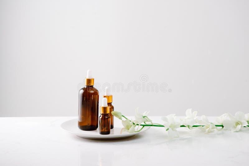 Бутылка капельницы масла органической орхидеи чистого на белой поверхности с головами орхидеи на заднем плане стоковые изображения