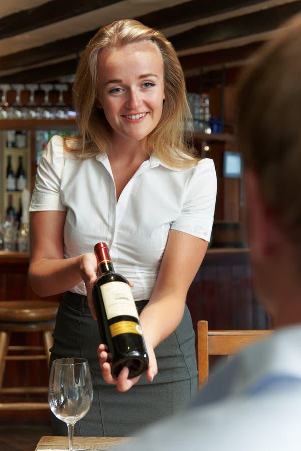 Бутылка клиента ресторана показа официантки красного вина стоковая фотография rf