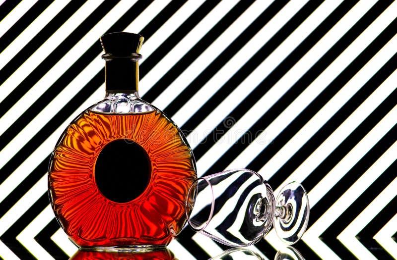Бутылка коньяка и стекло snifter против ясной абстрактной предпосылки стоковые изображения rf