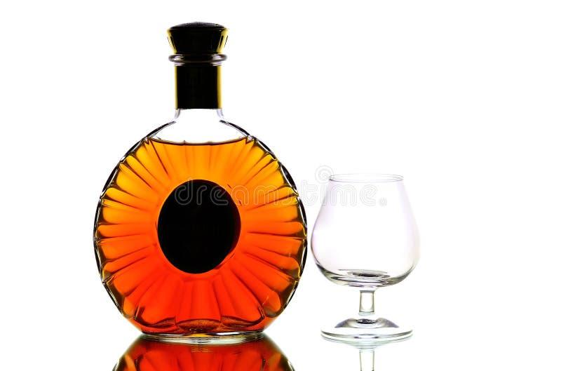 Бутылка коньяка и стекло snifter против ясной предпосылки стоковые фото