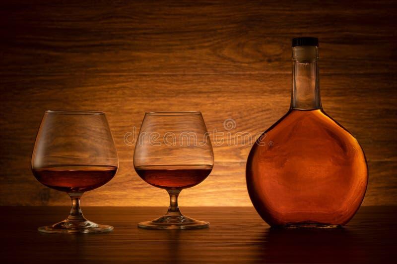 Бутылка коньяка с 2 стеклами на деревянной предпосылке стоковые фото