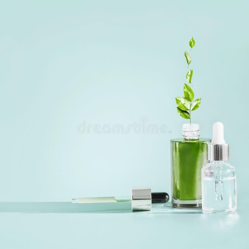 Бутылка косметик заботы кожи с капельницей и пипеткой на голубой предпосылке Естественные сыворотка или нефтяные продукты с зелен стоковые фотографии rf