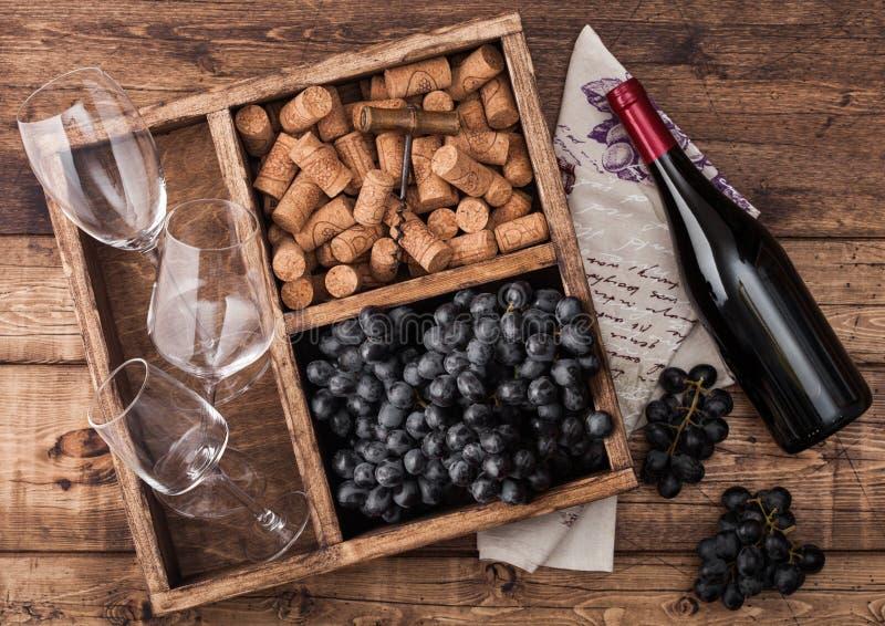 Бутылка красного вина на древесине с пустыми стеклами с темными виноградинами с пробочками и консервооткрывателем внутри винтажно стоковое изображение