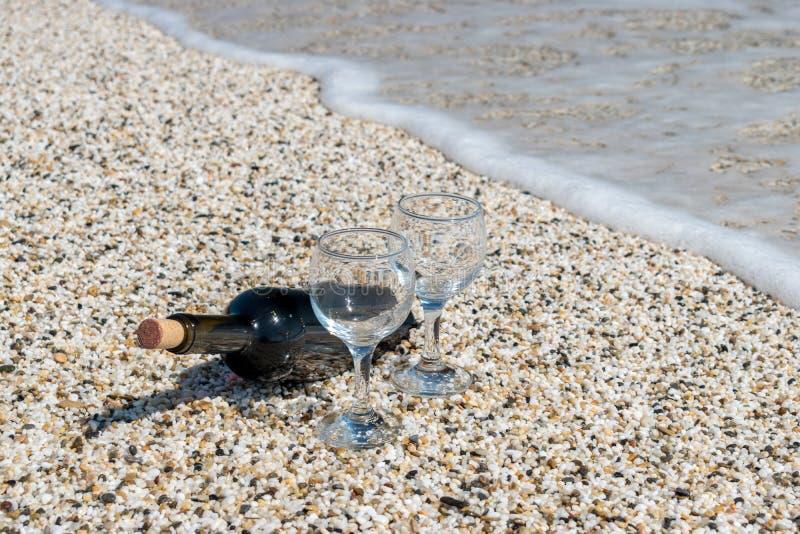 Бутылка вина на каменистом пляже фото