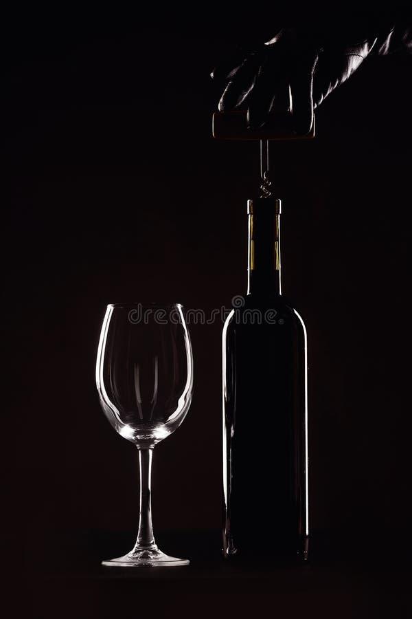 Бутылка красного вина с стеклом на черной предпосылке, руке с штопором стоковые фото
