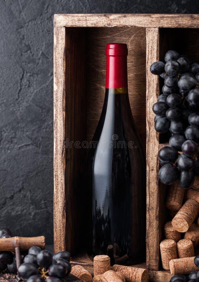 Бутылка красного вина с темными виноградинами и пробочками внутри винтажной деревянной коробки на черной каменной предпосылке r стоковые фото