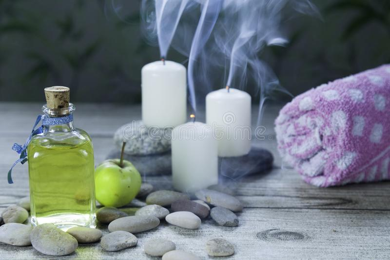 бутылка массажа масла яблока, камешков реки, небольших зеленых яблока и полотенца на деревянном столе и травяной стоковое фото rf