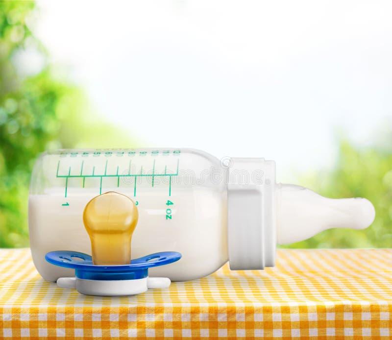 Бутылка молока младенца на светлой предпосылке стоковые фото
