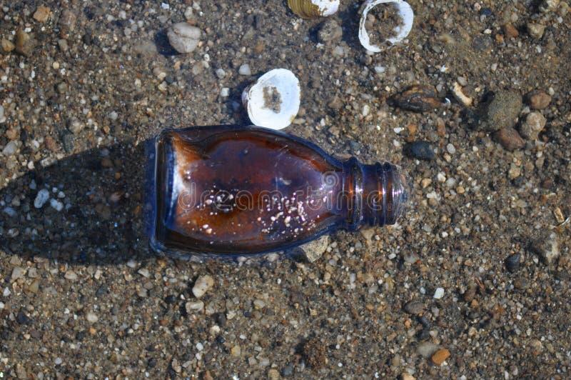 Бутылка погани на пляже стоковое фото