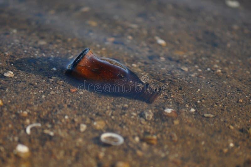 Бутылка погани на пляже стоковые фото