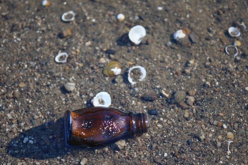 Бутылка погани на пляже стоковые изображения