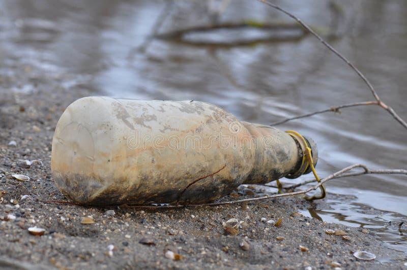 Бутылка погани на пляже стоковая фотография
