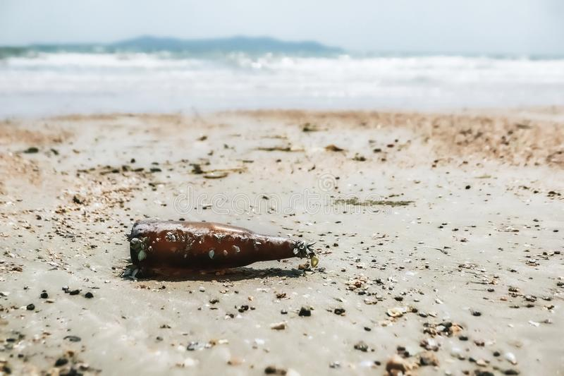 Бутылка погани стеклянная на пляже стоковое фото