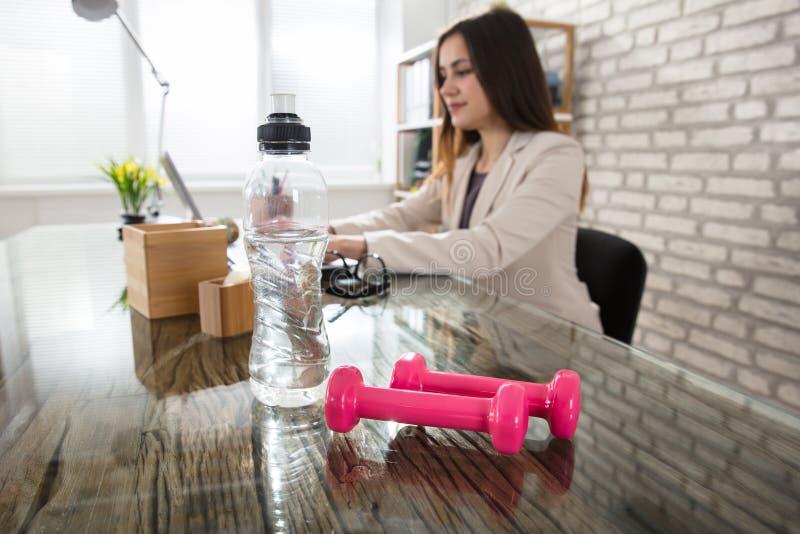 Бутылка с водой и розовые гантели на столе офиса стоковое изображение