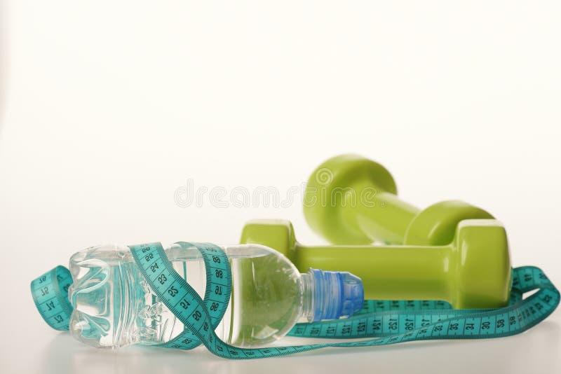 Бутылка с водой связанная с cyan лентой измерения зелеными гантелями стоковые фото