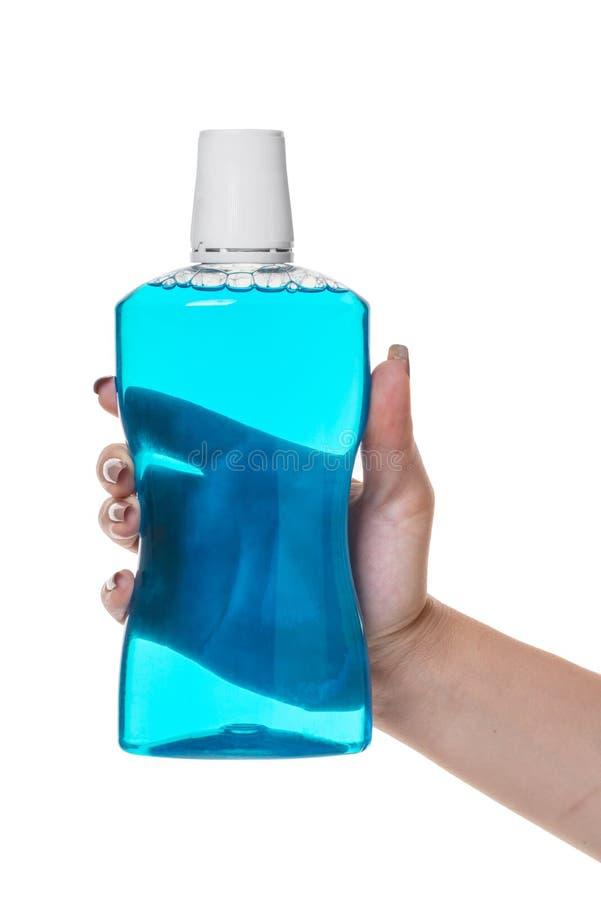 Бутылка с помощью rinse для рта в руке стоковая фотография