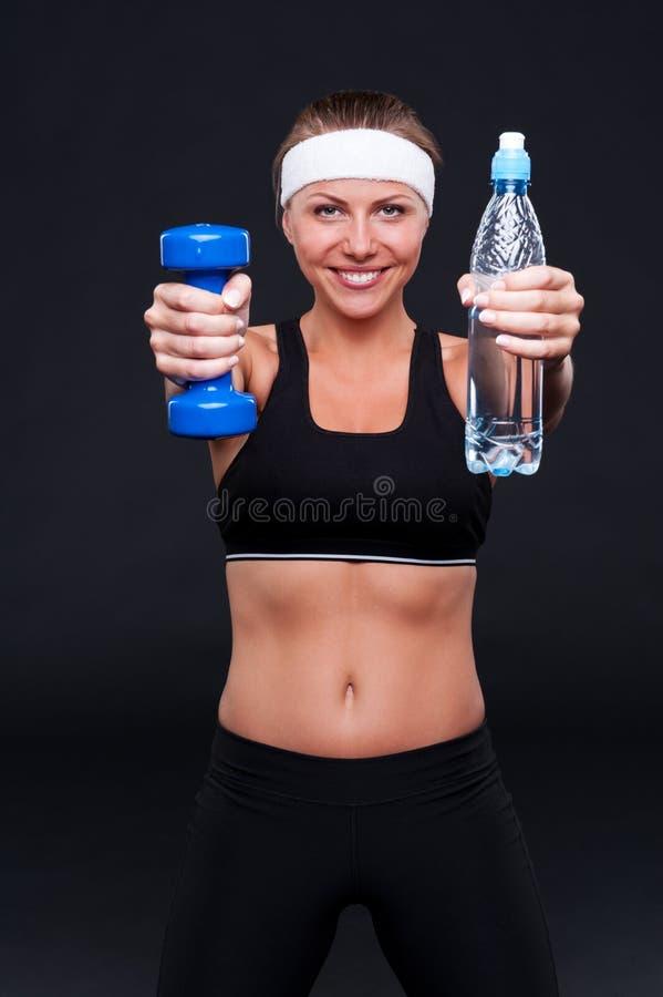 Бутылка удерживания женщины воды и веса стоковое изображение rf