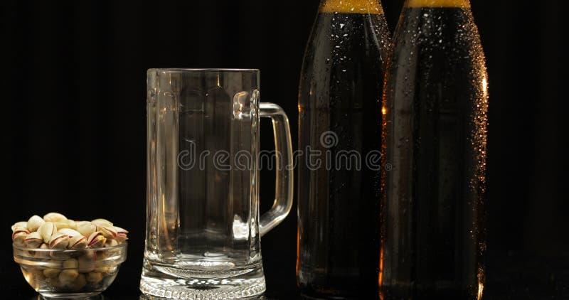 Бутылка 2 холодного пива на черной предпосылке Выпивая стекло и гайки фисташки стоковое фото rf