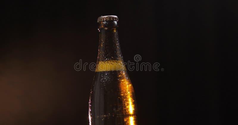 Бутылка холодного пива на черной предпосылке Конденсат стоковые фото