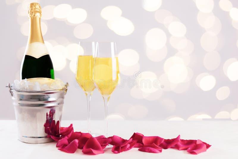 Бутылка Шампань в охладителе шампанского с лепестками розы против запачканной предпосылки стоковые фото