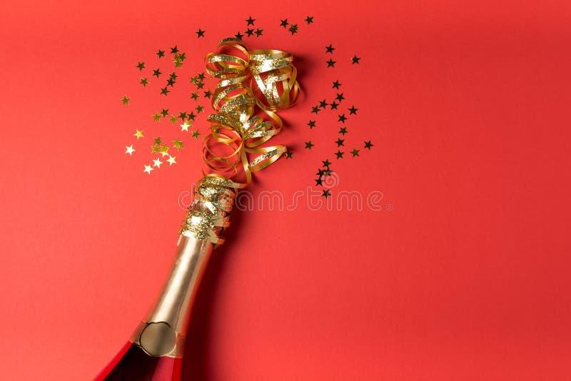 Бутылка Шампань с золотой лентой на красной бумажной предпосылке День Святого Валентина, день рождения, концепция торжества свадь стоковая фотография
