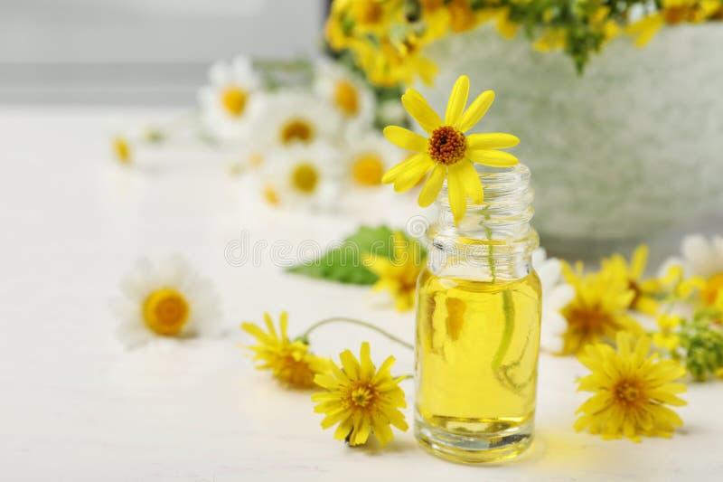 Бутылка эфирного масла с желтыми цветками на таблице стоковое изображение