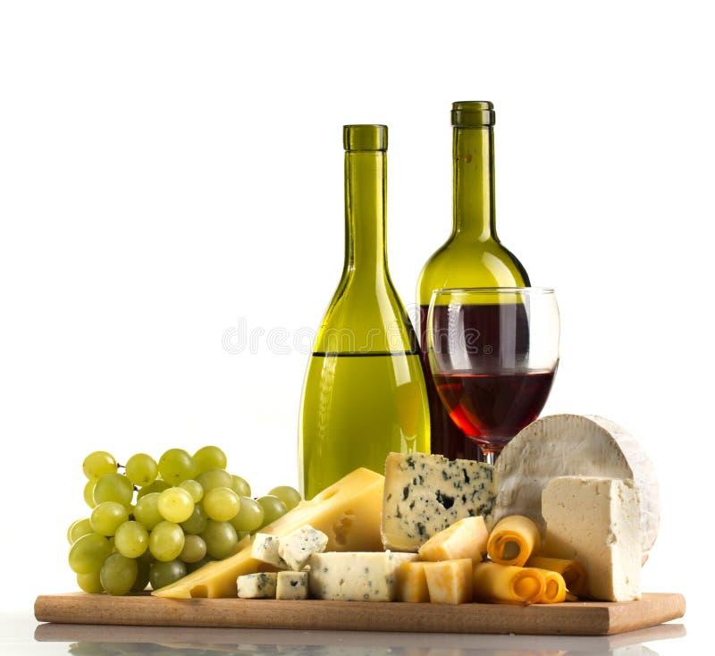 Бутылки вина, бокал, сыры и виноградина на стоковые фото