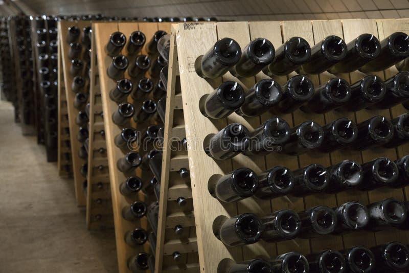 Бутылки игристого вина стеклянные заквашивая в погребе винодельни стоковые изображения