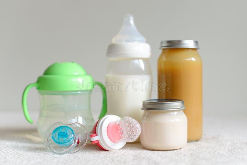 Бутылки молока, пюра и воды для младенца стоковое изображение
