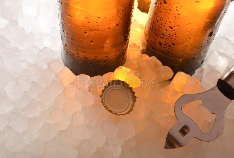 Бутылки стекла пива на льде с консервооткрывателем крышки и бутылки стоковые изображения rf
