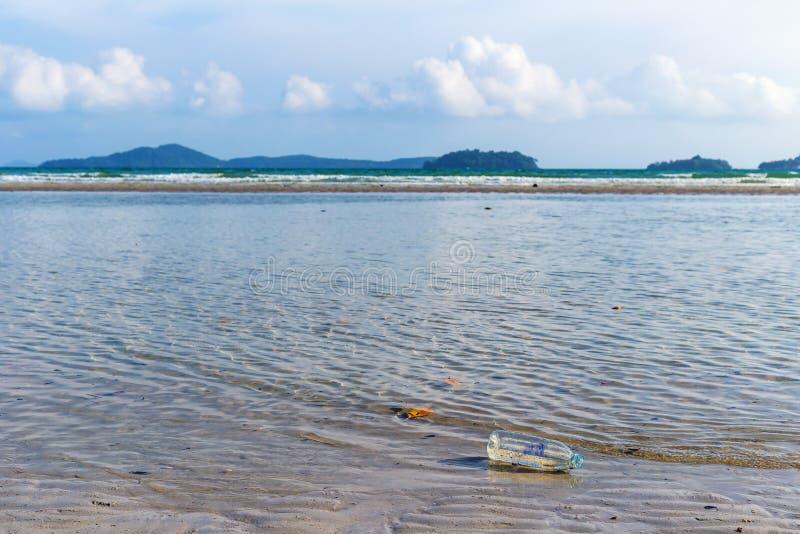 Бутылки сточных водов которые плавают на сторону пляжа, проблемы загрязнения окружающей среды от людей стоковая фотография
