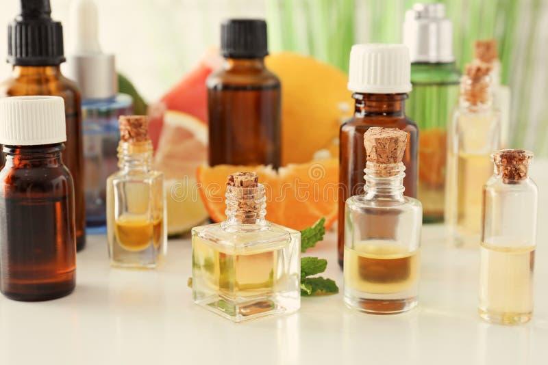 Бутылки с эфирными маслами цитруса на белой таблице стоковые фотографии rf