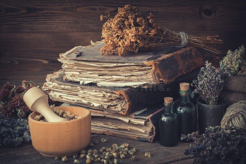 Бутылки тинктуры, пуки здоровых трав, стога античных книг, минометов, мешка целебных трав как обрабатывать perforatum микстуры hy стоковая фотография