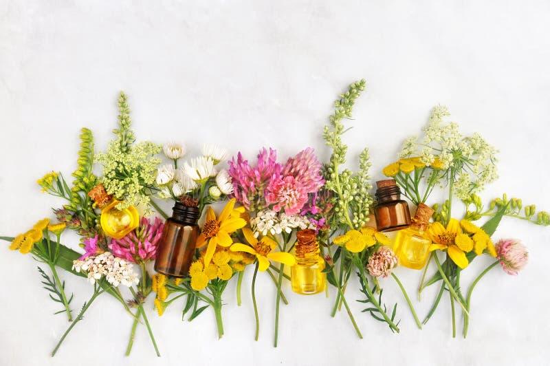 Бутылки эфирного масла и желтые цветки стоковые изображения rf