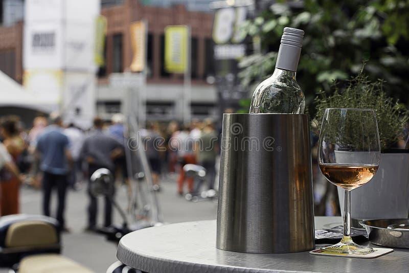 Бутылка вина в охладителе с стеклом подняла стоковое фото rf