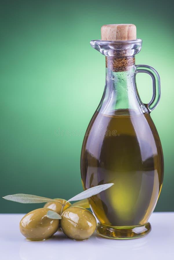 Бутылка и оливки оливкового масла на зеленой предпосылке стоковые фотографии rf